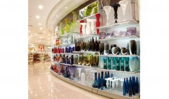 Espositore curvo con piani in vetro illuminati per arredo negozio con faretti