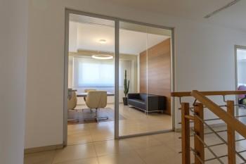 Sala riunioni parete divisoria in vetro tende tecniche tavolo e sedute - Riganelli Arredamenti
