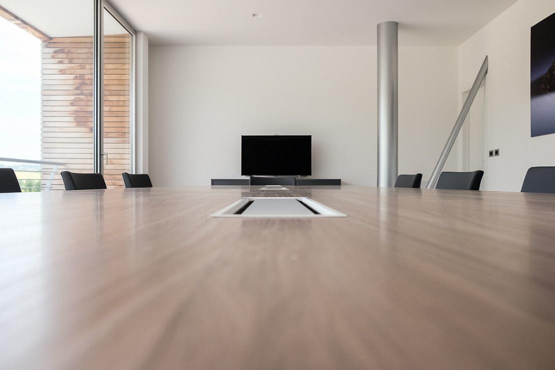 dettaglio arredamento sala riunione tavolo con passacavi e poltrone con ruote - riganelli