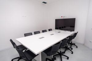 Sala riunione con tavolo sedute e monitor - riganelli